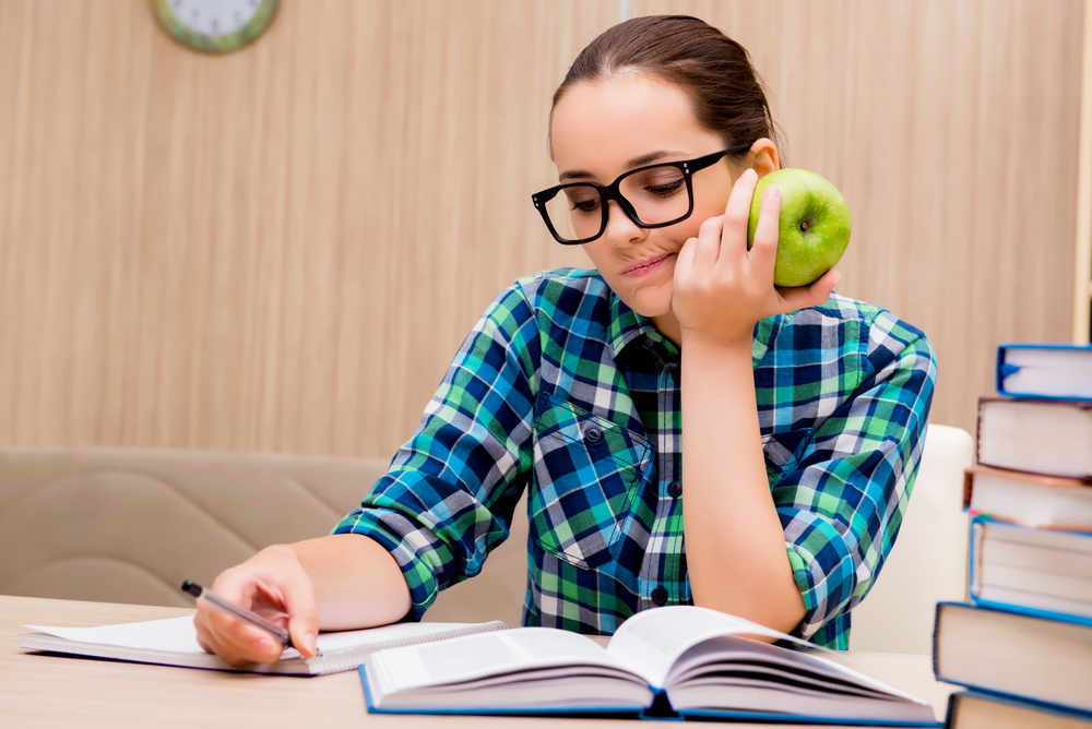 student eats an apple while studying for the bar exam